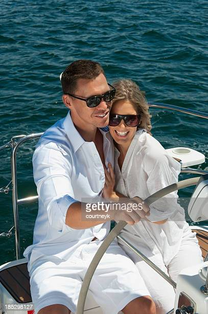 Happy couple driving a sailboat