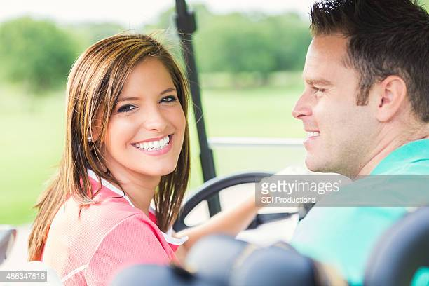 Happy couple driving golf cart while playing on green course