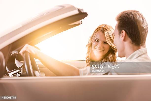 Happy couple driving in a convertible car at sunset.