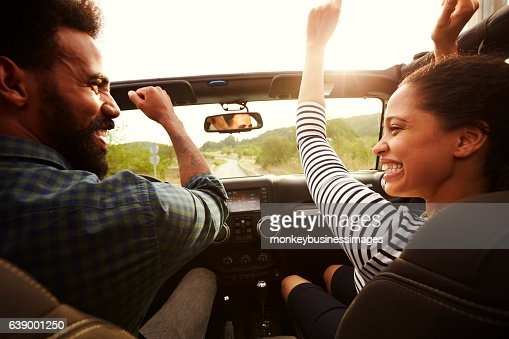 Happy couple driving in their car with arms in the air : ストックフォト