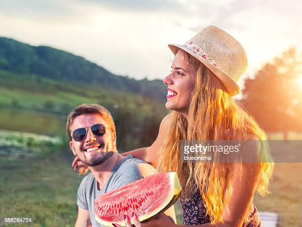 Happy couple eating watermelon
