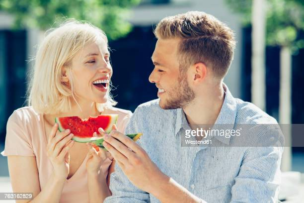 Happy couple eating watermelon together