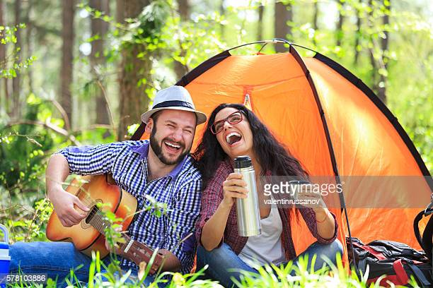 Happy couple enjoying a coffee time in the forest