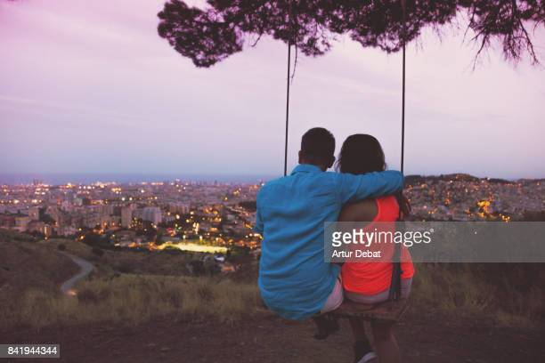 Happy couple enjoying a unique swing on a tree on top of Barcelona mountain contemplating the city at sunset with elevated point of view during summer good vibes in a romantic place.