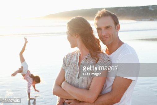 Happy couple enjoying on beach with daughter playing in the background : Stock Photo