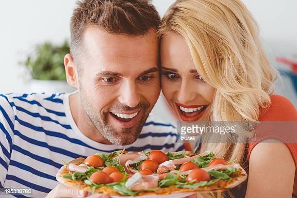 Happy couple enjoying pizza