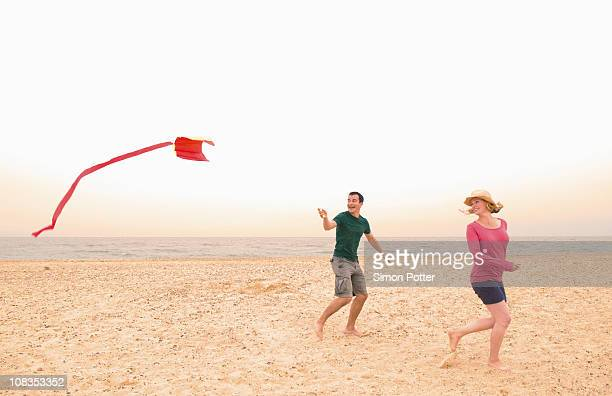 Happy couple fly kite on beach