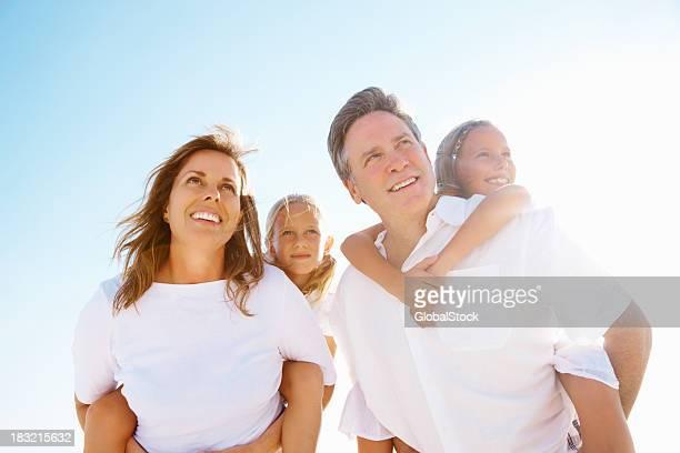 couple heureux pour porter sur le dos jusqu'à leurs enfants contre le ciel