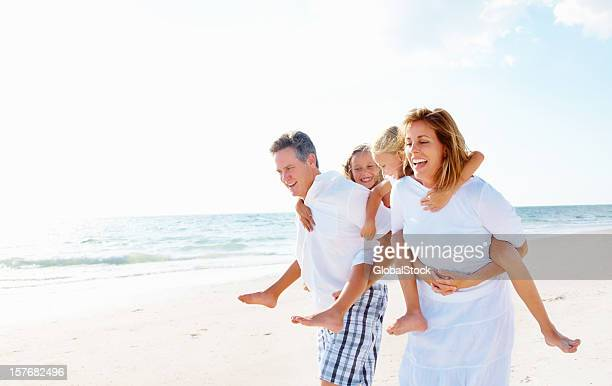 Happy couple giving piggyback ride to their children on beach
