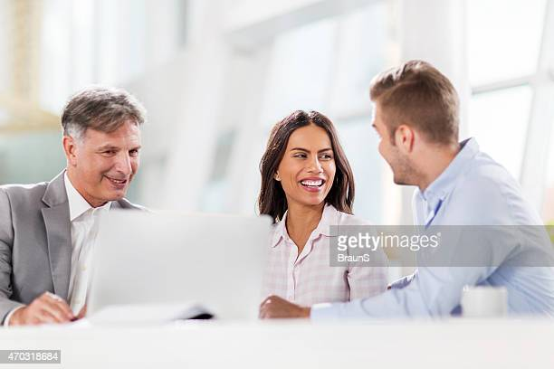 Happy couple having a business meeting with real estate agent.