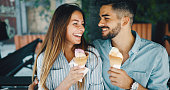 Happy young couple having date and eating ice cream