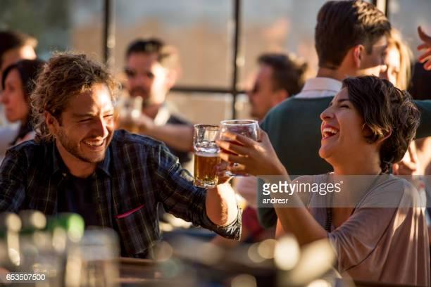 Pareja feliz tener bebidas en un bar