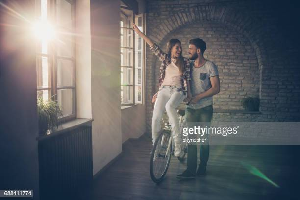 Happy couple having fun on a bike at empty apartment.