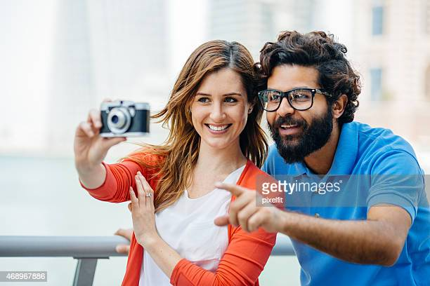 Happy couple having fun with retro camera outdoors