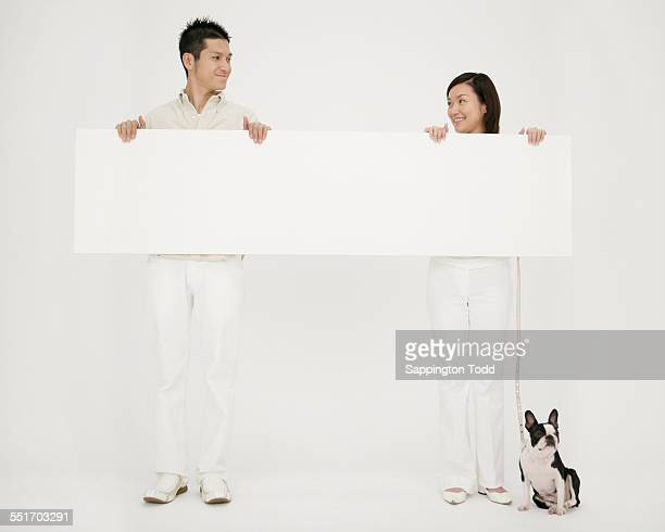 Happy Couple Holding Blank Placard With Their Dog