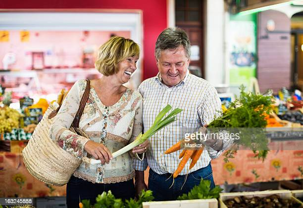 Happy couple holding carrots and spring onion at shop