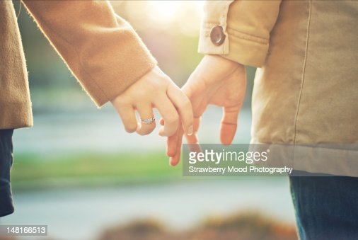 Happy couple holding hands in sunset light