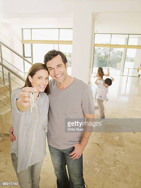 Happy couple holding keys in new house