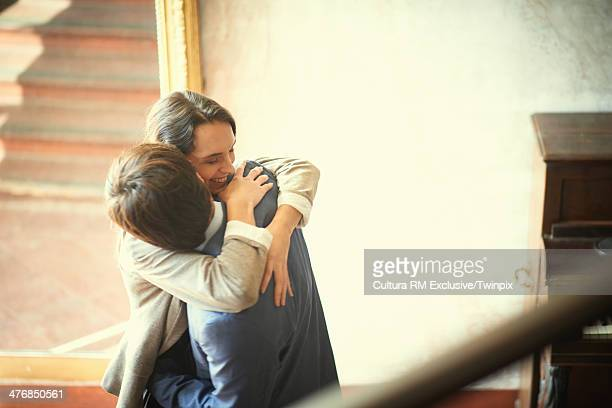 Happy couple hugging in apartment lobby