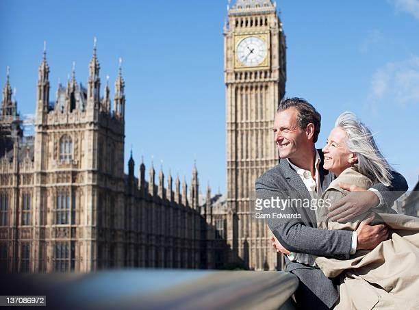 Happy couple hugging in front of Big Ben clocktower in London