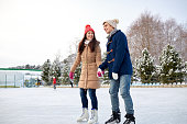 people, winter, friendship, sport and leisure concept - happy couple ice skating on rink outdoors