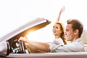 Happy couple in a convertible car at sunset.