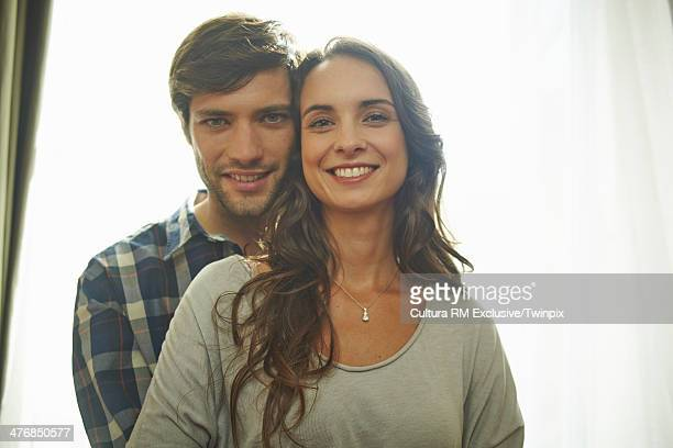 Happy couple in front of apartment window