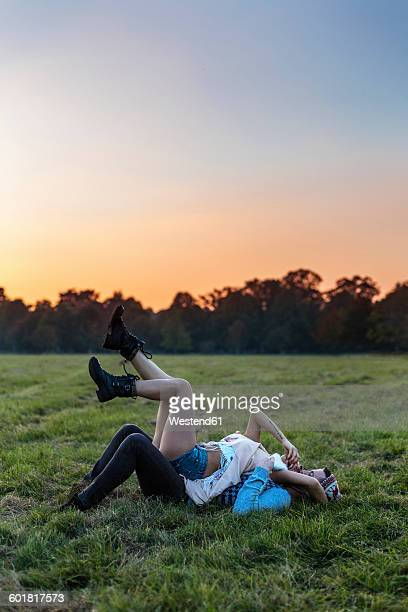 Happy couple in love lying on a meadow at sunset