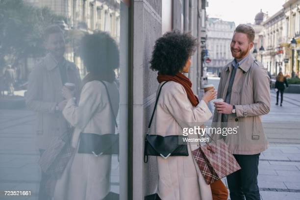 Happy couple in the city with takeaway coffee and shopping bags