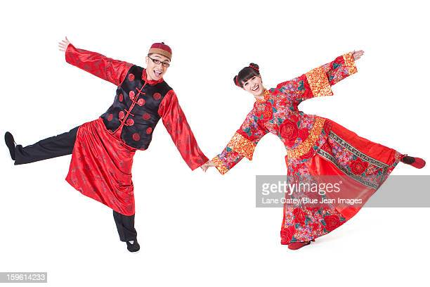 Happy couple in traditional Chinese clothing holding hands