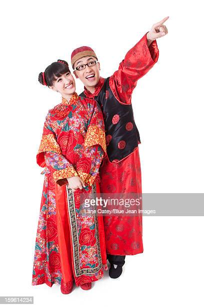Happy couple in traditional Chinese clothing pointing away