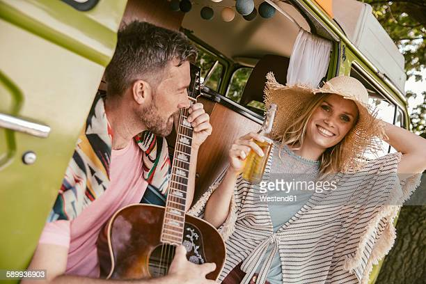Happy couple in van making music