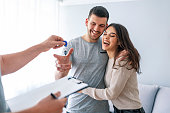 Happy couple is taking keys from their new house from broker and smiling. Hands of estate agent giving keys to the couple. The agent handed the keys a young couple
