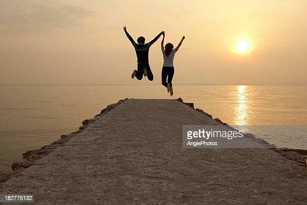 Glückliches Paar springen am Anlegesteg