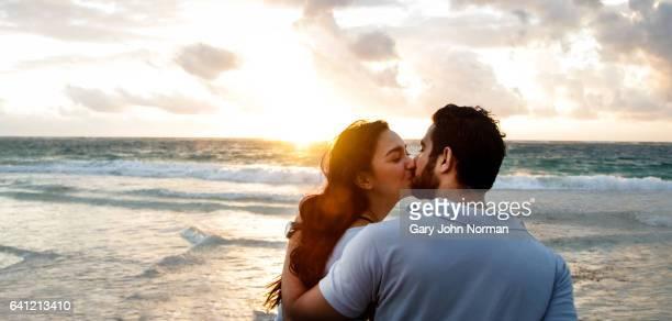 Happy couple kissing on beach.
