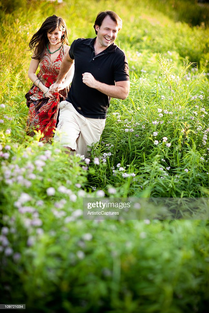 Happy Couple Laughing and Running Through Field of Wildflowers : Stock Photo