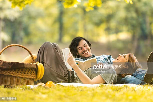 Happy couple laughing while reading book at picnic.