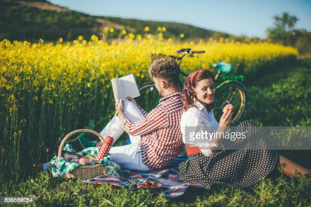 Happy couple laughing while reading book at picnic