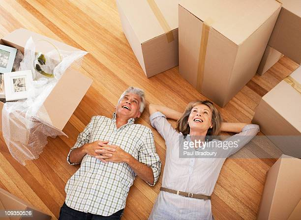 Happy couple laying on floor of new house