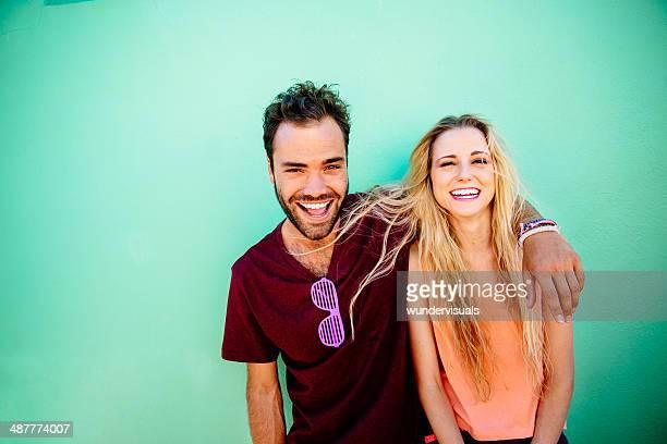 Glückliches Paar schiefen gegen Grüne Wand