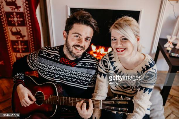 Happy couple looking at camera, while sitting in front of a fireplace, boyfriend playing guitar, xmas deocration