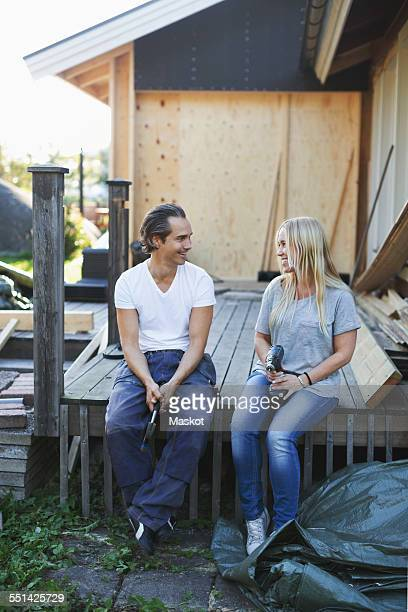 Happy couple looking at each other outside house during home improvement