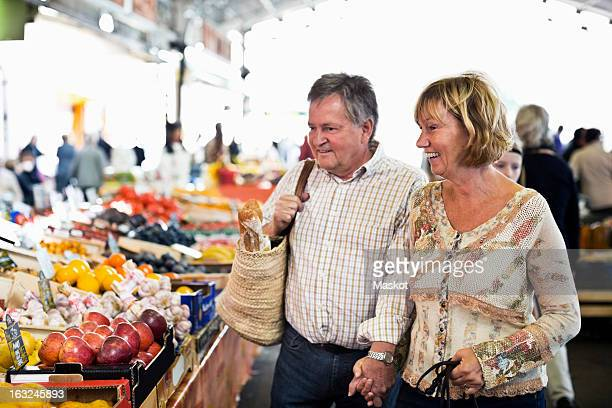 Happy couple looking at fruits in market