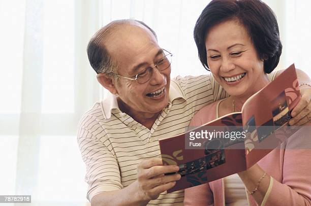 Happy Couple Looking at Travel Brochure
