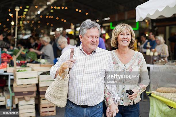 Happy couple looking away with market in the background