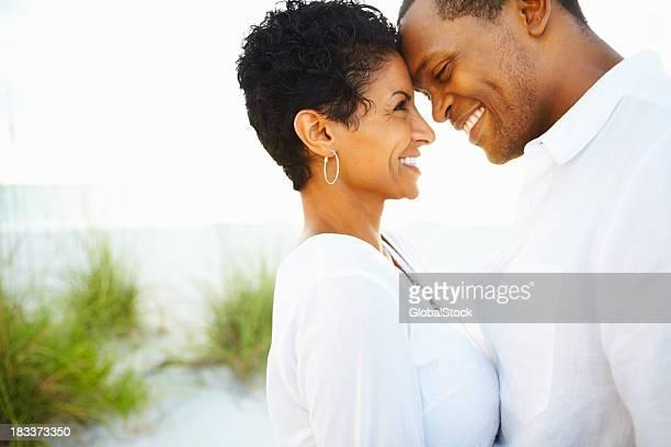 Glückliches Paar suchen in jeweils anderen Augen an der Küste