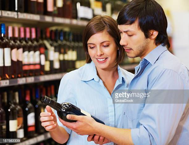 Happy couple looking out for a wine bottle at supermarket