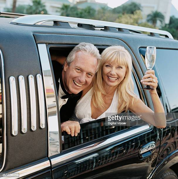 Happy Couple Looking Out of a Limousine Window, the Woman Holding a Champagne Glass
