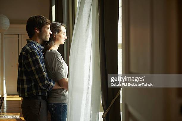 Happy couple looking out of apartment window