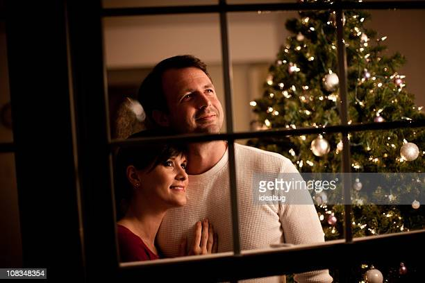 Happy Couple Looking Out Window with Christmas Tree Behind